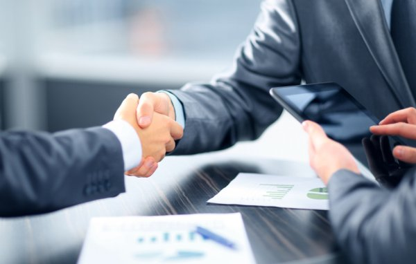 Two men in business clothes shake hands.