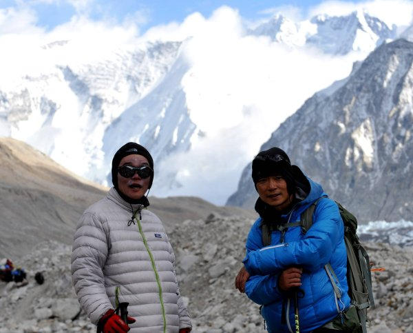Two asian men standing in front of mountains in the Himalaya.