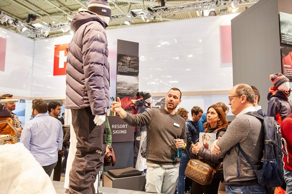Two men are looking at ski jacket at a booth