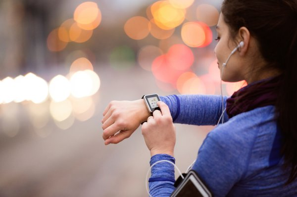 Woman with heart rate monitor and Smartwatch jogging
