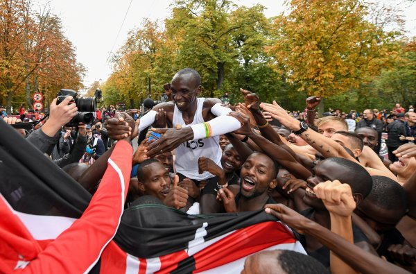 Behind the finish line, Eliud Kipchoge celebrates with his team.