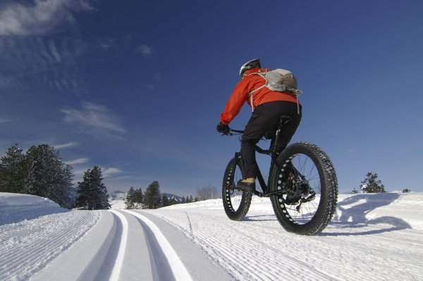 A fatbiker is racing through the snow.