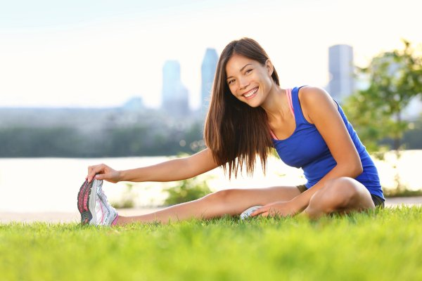 An Asian female athlete stretches in the park.