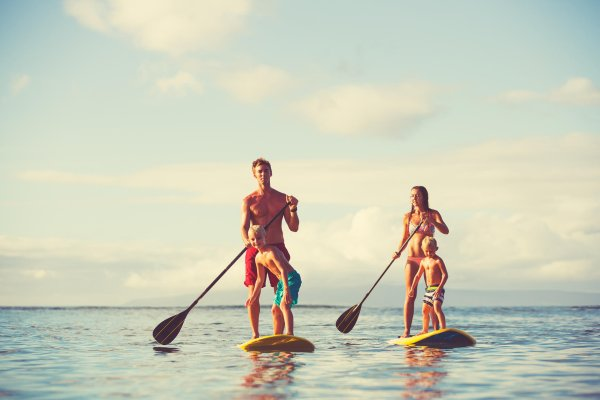 A man and a woman are stand-up-paddling with childeren