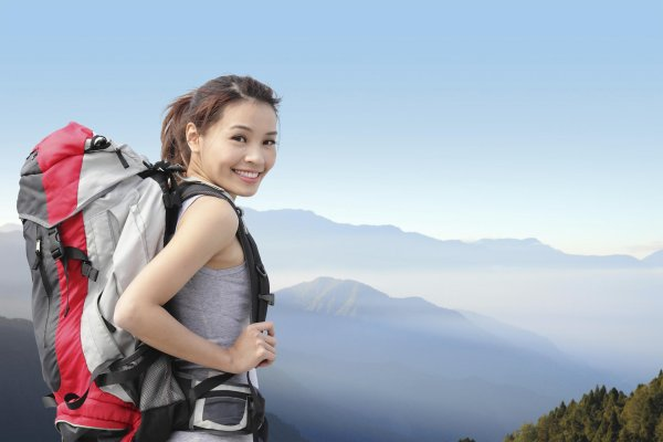 Woman with a big backpack on a mountain.
