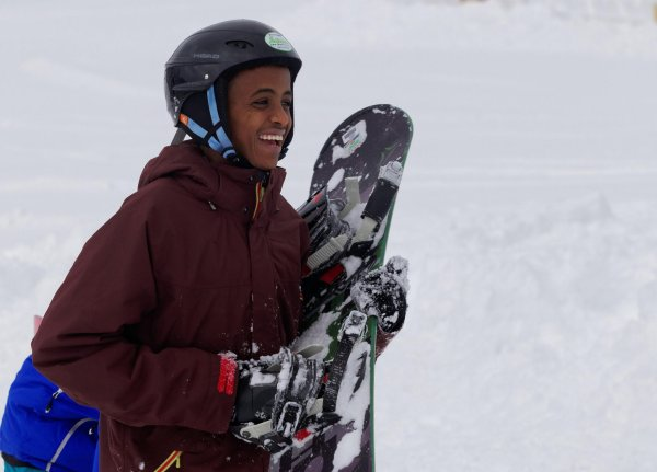 A refugee holding a snowboard and looking happy