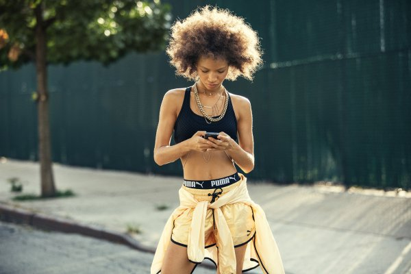 Girl in a sportdress with a smartphone in her hand.