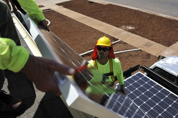 Workers install the solar cells on the houses