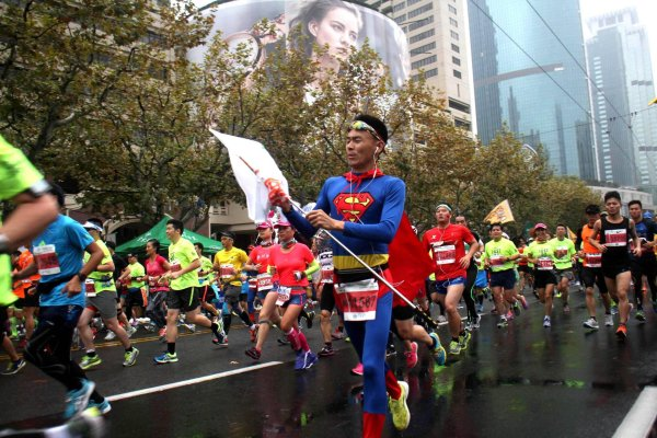 A Chinese man dressed as Superman running at the Marathon Shanghai.