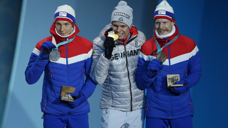 Yeah, the medal's real. Andreas Wellinger, Olympic champion in ski jumping from the normal hill, with the obligatory bite in his gold medal. With him on the podium the two Norwegians Johann André Forfang and Robert Johansson