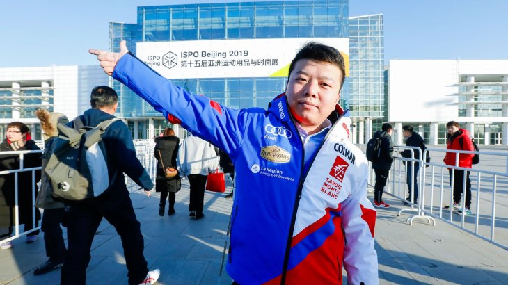 The jacket is needed in cold Beijing: A visitor greets friendly at the entrance of the fair.