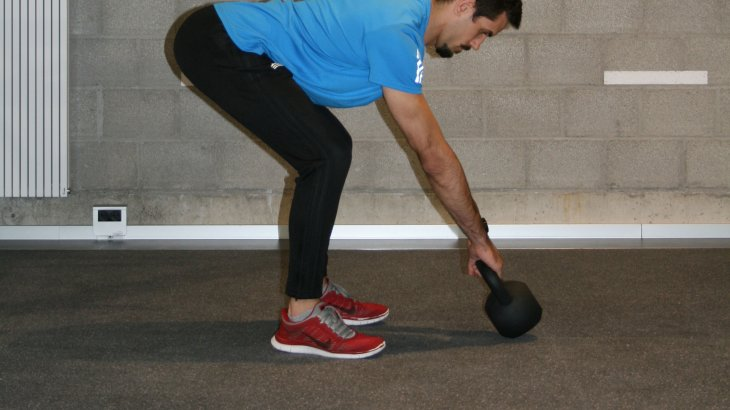 Bend forward from the hip and grab the ball, tilting it up. Pulling the shoulder blades together brings the ball into the correct distance from the body. And also, tense up your stomach like you're expecting a punch.