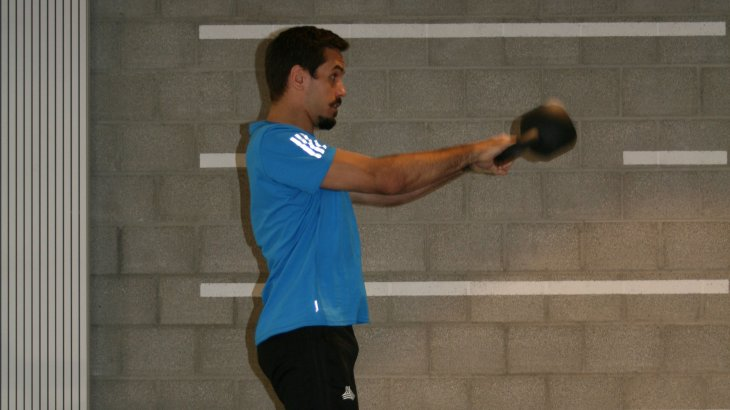 Raise the torso slightly and swing the ball between the legs. Simultaneously with the forward movement of the kettlebell, stretch the hips and knees explosively.