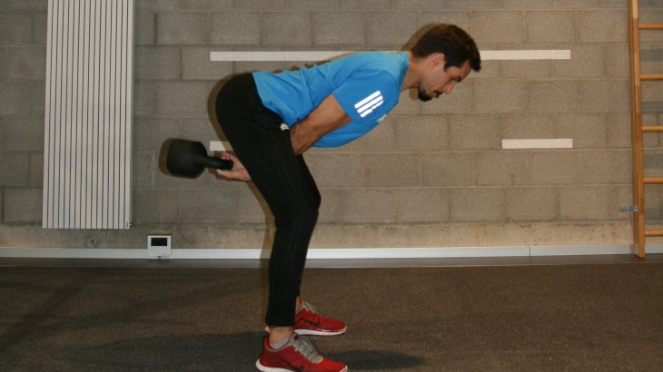 When the ball swings back between the legs, the hip bends quickly and intercepts the swing of the ball. Accelerate the kettlebell again or swing it to the end.