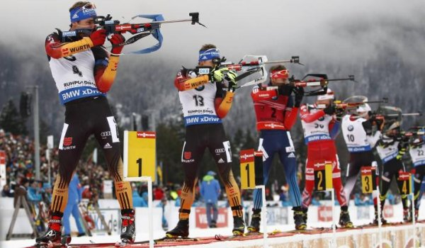 Biathletes stand in line and shoot.