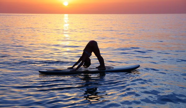 SUP-Yoga promotes concentration and balance, since the exercises are carried out on the water on a surfboard.