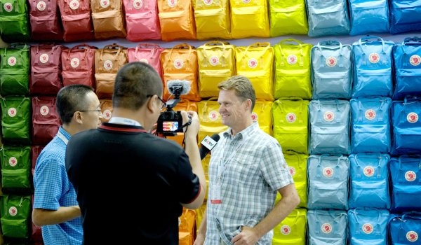 / Fjällraven chooses a more classic approach. Video message in front of the rainbow backpack wall