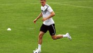 Defender Matthias Ginter naturally looks at the ball on a football field.