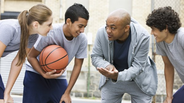 Four people talking after playing basketball.