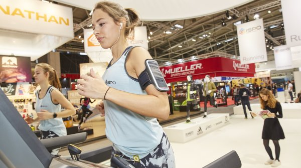 Woman running on treadmill at ISPO Munich.