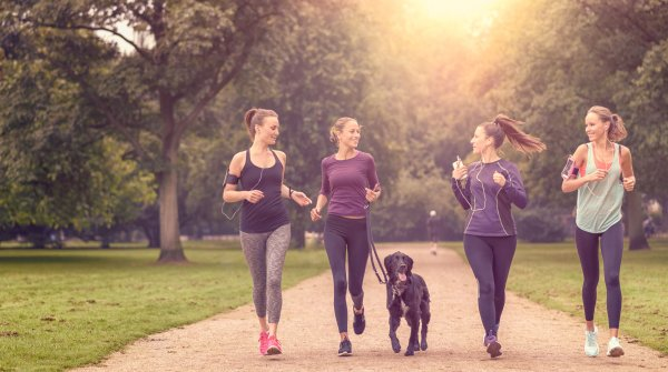 Four women and a dog are jogging together in the park