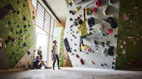 Sportler beim Bouldern an der Kletterwand