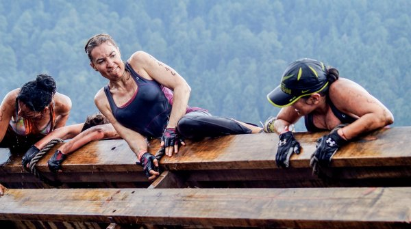 Three women climbing an obstacle