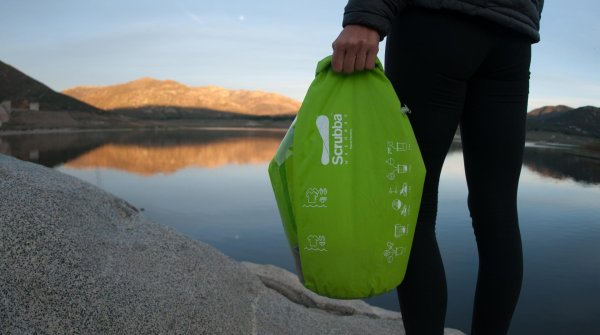 Scrubba Wash Bag with lake scenery in the background.