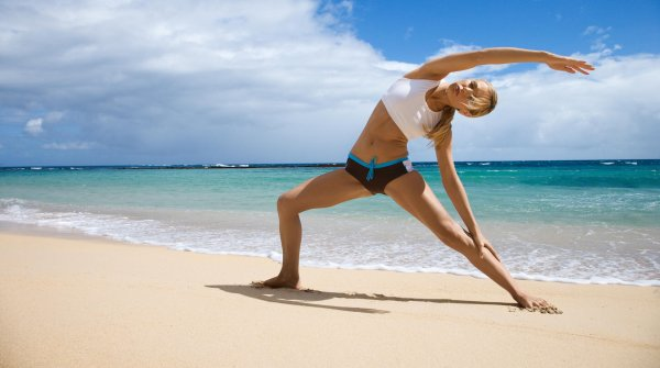 A woman practices yoga at the beach.