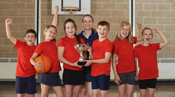 Kids and their teacher cheering after a basketball-game with a trophy.