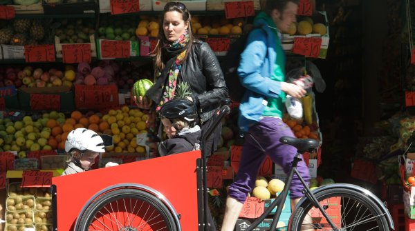 Mother with child in front of a greengrocer's shop