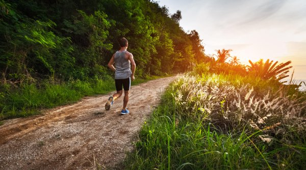 Runner trains aerobically on a path in nature