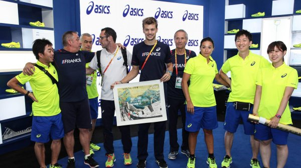France's sprinter Christophe Lemaitre (middle) stands with the running experts under contract of Asics
