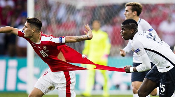 Paul Pogba (right) rips the shirt of Switzerland star Granit Xhaka.