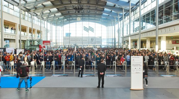 Countless visitors wait in the entrance hall for the trade fair to begin.