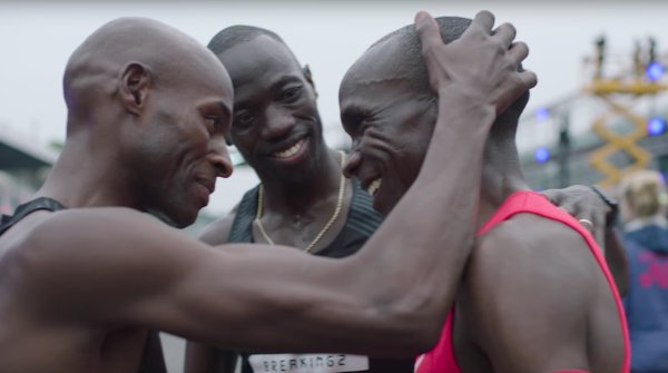 "Eliud Kipchoge (right) is congratulated by his pacemaker after the ""Breaking2"" run."